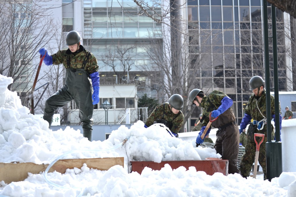 Members of the Japan Self Defense Forces work near a large snow sculpture they are building.