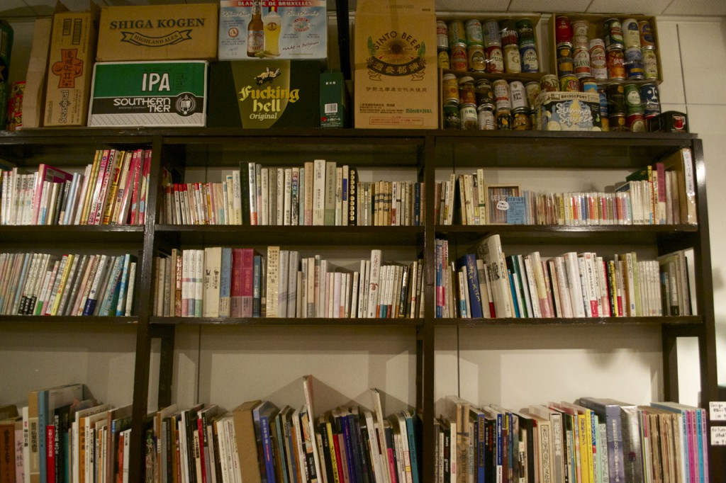 Bookshelves and beer boxes line the wall.