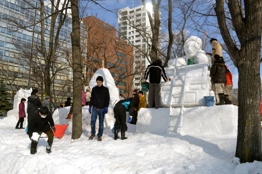 A group works on a sculpture, collecting snow from the nearby sidewalk to complete the job.