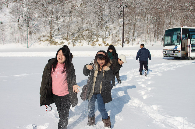 Tourists from Asia enjoy the snow